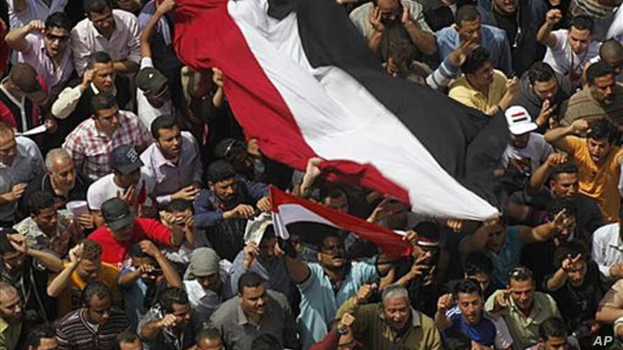 Egyptians shout as they wave a giant flag during a demonstration at Tahrir Square, Cairo, April 1, 2011, to call for the military government to harshly punish members of ex-President Hosni Mubarak's former administration