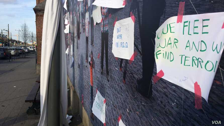 Refugees and other migrants post signs outside the temporary housing camp against terrorism after the Brussels attacks that killed 35 people and wounded more than 300, March 26, 2016. (VOA/H. Murdock)