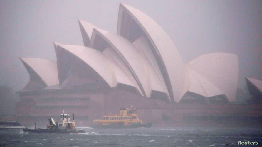 Ferries and boats pass in front of the Sydney Opera House as strong winds and heavy rain hit the city of Sydney, Australia, Nov. 28, 2018.
