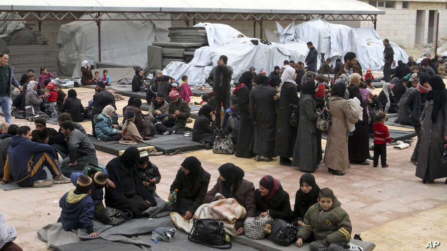 FILE - Displaced Syrian families take refuge in a school that has been turned into a temporary shelter in the Qudsaya neighborhood on the outskirts of Damascus, Syria, Feb. 23, 2015. Monitors say hundreds of civilians fled villages in the Barada Vall