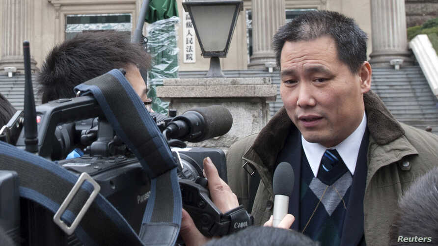 FILE - Chinese lawyer Pu Zhiqiang (R) speaks to journalists outside a courthouse in Chongqing municipality.