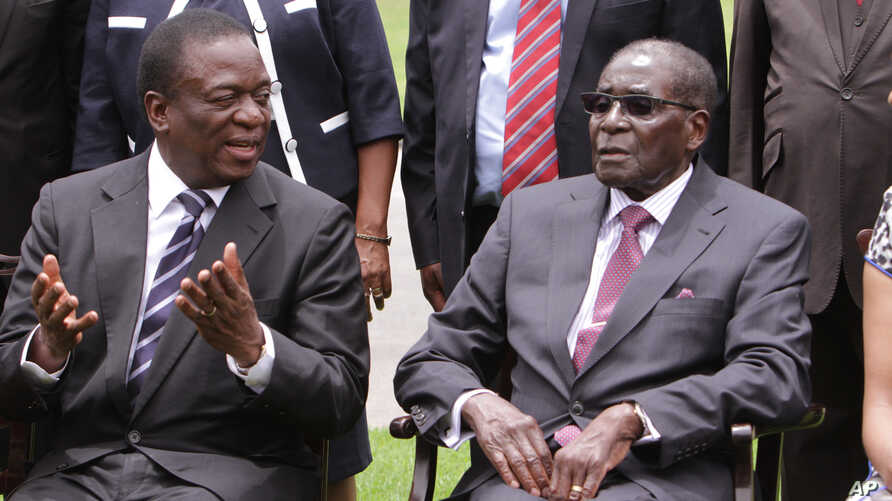 Emmerson Mnangagwa, left, Vice President of Zimbabwe chats with Zimbabwean President Robert Mugabe after the swearing in ceremony at State House in Harare, Dec, 12, 2014.