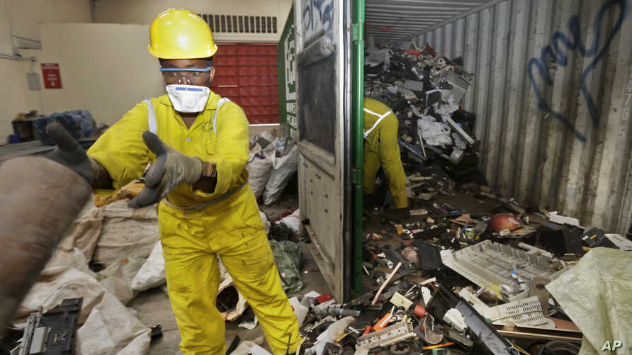 FILE - Workers unload and sort through a container full of electronic waste that was collected from a Nairobi slum and brought in for recycling, at the East African Compliant Recycling facility in Machakos, near Nairobi, in Kenya, Aug. 18. 2014.