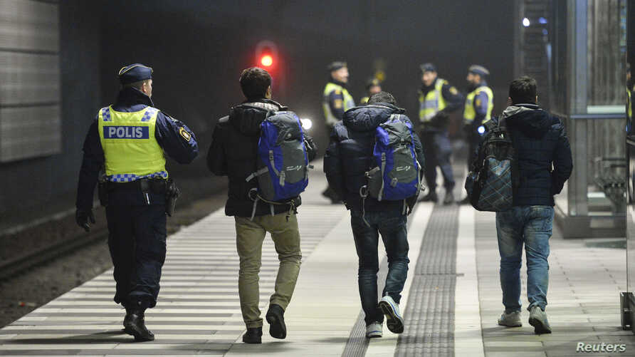 A police officer escorts migrants from a train at Hyllie station outside Malmo, Sweden, Nov. 19, 2015.