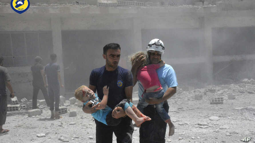 This photo provided by the Syrian Civil Defense group known as the White Helmets, shows civil defense workers carrying children after airstrikes hit a school housing a number of displaced people, in the western part of the southern Daraa province of