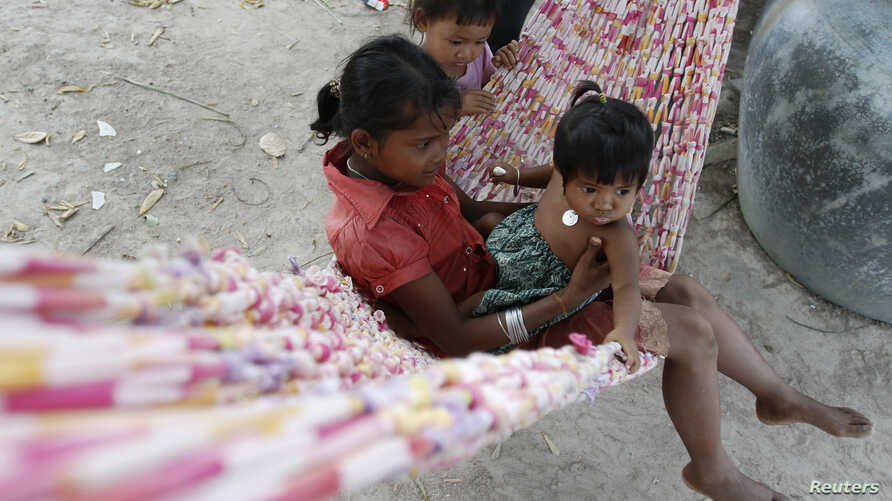 Children play in a hammock in Broma village in Kratie province, Cambodia, Oct. 22, 2012.