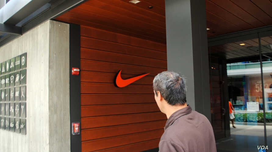 FILE - A man passes a Nike store in Los Angeles, California. (Photo by Diaa Bekheet)
