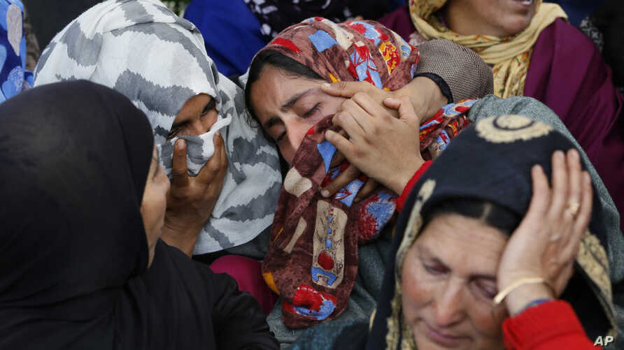 An unidentified relative is comforted by Kashmiri villagers as she grieves near the dead body of Sarjeel Sheikh, a civilian who was shot during a protest near the site of gunbattle in Khudwani village about 60 kilometers (37 miles) south of Srinagar,