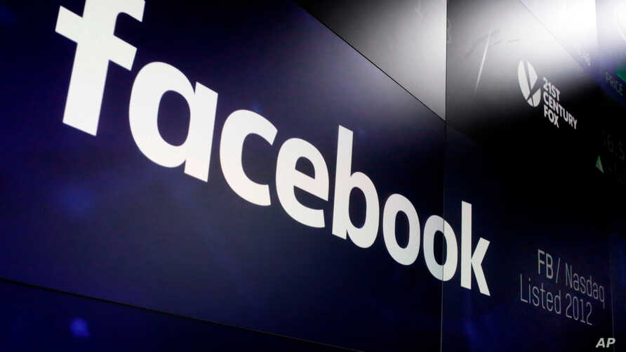 """FILE- The logo for Facebook appears on screens at the Nasdaq MarketSite in New York's Times Square, In this March 29, 2018. A report says Facebook and the FTC are negotiating a """"multibillion dollar"""" fine for the social network's privacy lapses."""