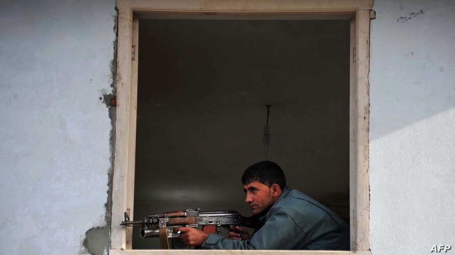 An Afghan policeman takes position at the site of a suicide attack in Jalalabad, March 26, 2012.