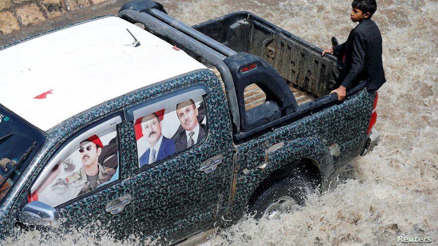 FILE - A vehicle with posters of Yemen's former president Ali Abdullah Saleh and his eldest son, Ahmed, on its window glass drives in floodwater during a rainy day in the old quarter of Sanaa, Yemen, Aug. 9, 2017.