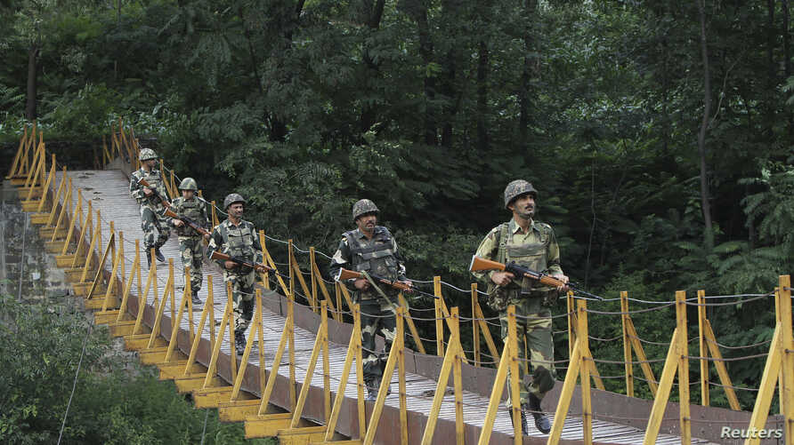 FILE - Indian Border Security Force soldiers patrol over a footbridge built over a stream near the Line of Control, a cease-fire line dividing Kashmir between India and Pakistan, at Sabjiyan sector of Poonch district, August 2013.