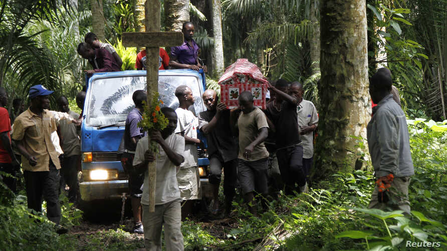 Relatives and friends carry the body of Yvonne Masika, who was killed during an attack by suspected ADF-NALU rebels, for burial in Mbau village near Beni, in North Kivu province, DRC, Oct. 21, 2014.