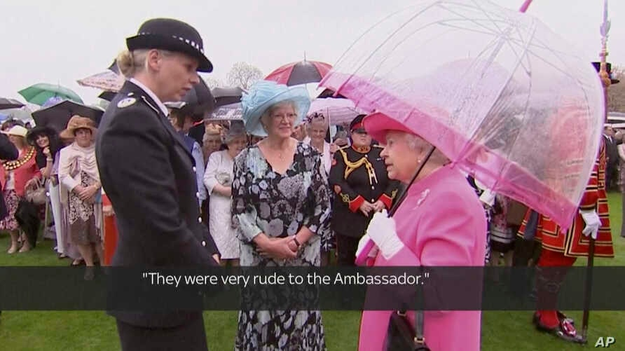 """In image made from pool video, Queen Elizabeth II speaks with Metropolitan Police Commander Lucy D'Orsi in the garden of Buckingham Palace in London, May 10, 2016. The queen was overheard on video describing Chinese officials as """"very rude to the amb"""