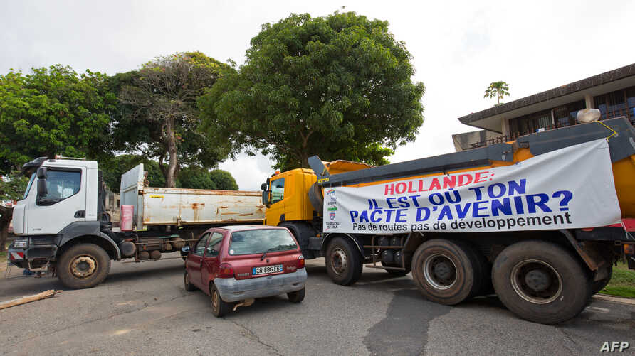 "Trucks form a blockade in Cayenne on March 26, 2017, with a banner reading ""Hollande (refering to French president Francois Hollande), where is your deal on the future ? No roads, no development""."