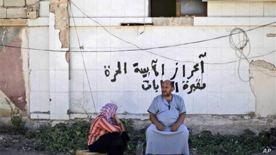 A Syrian couple, who fled their home, sits on the side of the road as they take refuge at the Bab Al-Salameh border crossing in hopes of entering one of the refugee camps in Turkey, near the Syrian town of Azaz, August 23, 2012.