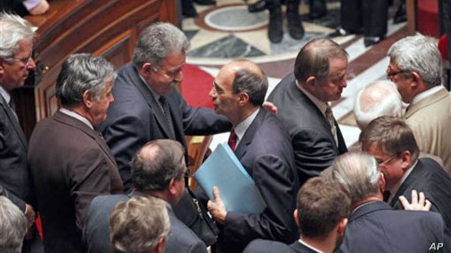 French Labor Minister Eric Woerth, center, is congratulated by members of parliament after the vote on retirement reform at the National Assembly in Paris, 27 October 2010