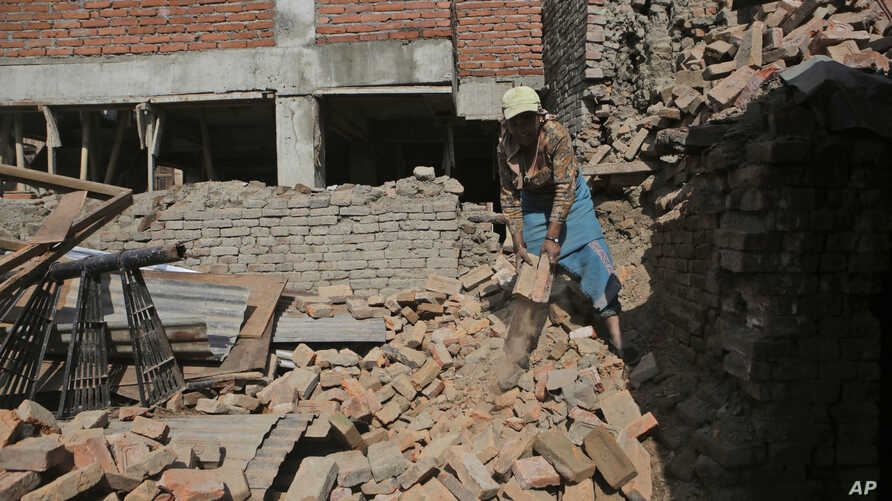 A Nepalese woman collects bricks from a destroyed building in Bhaktapur, Nepal, April 24, 2017. Nepal's government has been criticized for moving slowly in dispersing funds that would allow people to rebuild.