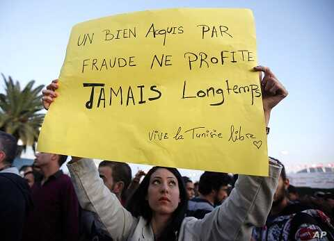 """A Tunisian demonstrator holds a sign that says """"things acquired fraudulently never last long"""" during a protest against the Islamist Ennahda movement in Tunis, October 26, 2011."""