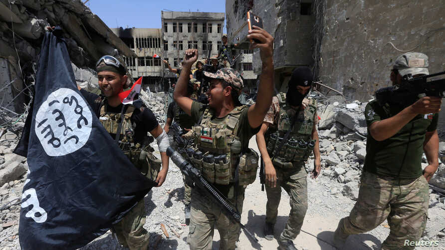 Members of the Emergency Response Division hold an Islamic State flag that they pulled down as they celebrate in the Old City of Mosul, Iraq, July 8, 2017. Islamic State fighters have mostly been pushed out of Iraq and Syria but are far from defeated