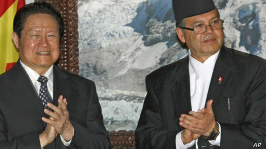 Nepal's Prime Minister Jhalanath Khanal, right, and Zhou Yongkang, special envoy of Chinese President Hu Jintao, applaud after signing an agreement on economic cooperation, in Katmandu, Nepal, Aug. 16, 2011. Zhou arrived Tuesday on a three-day offici
