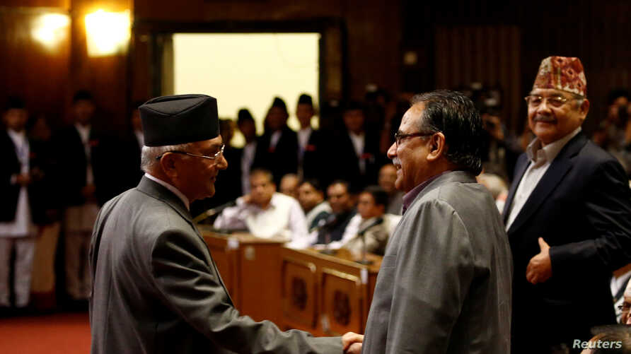 Nepal's Prime Minister Khadga Prasad Sharma Oli, also known as KP Oli, shakes hand with Chairman of the Unified Communist Party of Nepal (Maoist) Pushpa Kamal Dahal, also known as Prachanda, (R) as he returns after announcing his resignation at the p
