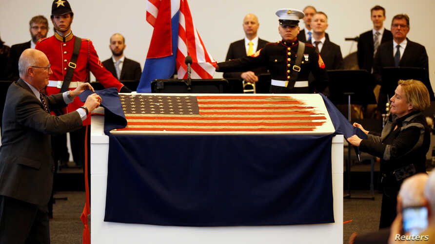 Netherland's Minister of Defence Ank Bijleveld-Schouten and U.S. ambassador Pete Hoekstra (L) unveil an American flag from Navy ship LCC 60 that led the U.S. invasion fleet at Normandy's Utah Beach is displayed during the 75th anniversary of the D-Da
