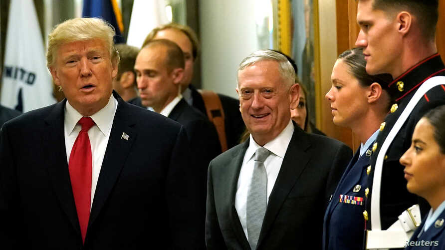 Secretary of Defense James Mattis, right, escorts U.S. President Donald Trump as he greets military personnel after attending a meeting at the Pentagon in Arlington, Virginia, July 20, 2017.