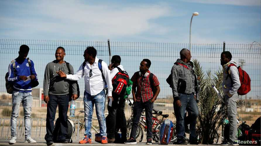 FILE - African migrants stand outside the Holot detention center in Israel's Negev desert, March 13, 2018.