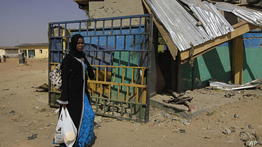 An unidentified woman walks past the ruins of a market outside the state police headquarters in Kano, Nigeria. Police said that members of the radical Islamist group Boko Haram dressed in uniforms resembling those of soldiers and police officers when