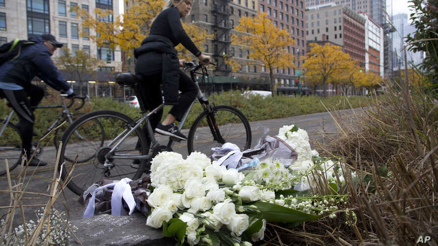 A bicyclist passes bouquets of flowers left by Argentine President Mauricio Macri and New York Mayor Bill de Blasio at the site of the terrorist attack, Nov. 6, 2017, in New York. Five Argentine bicyclists were among eight people killed by the terror...