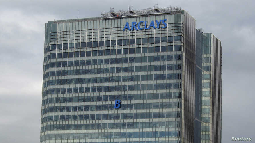 The letter 'B' of the signage on the Barclays headquarters in Canary Wharf is hoisted up the side of the building in London, July 20, 2012.