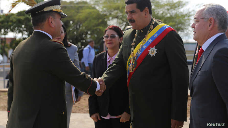 Venezuela's President Nicolas Maduro, right, shakes hands with Venezuela's Defense Minister Vladimir Padrino Lopez as he arrives to  commemorate the Battle of San Felix,  April 11, 2017.