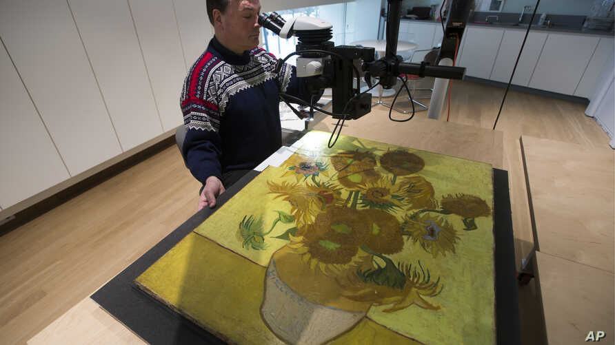 "Senior paintings conservator Rene Boitelle works on restoring Vincent van Gogh's world-famous ""Sunflowers"" painting at the Van Gogh museum in Amsterdam, Netherlands, Jan. 23, 2019."