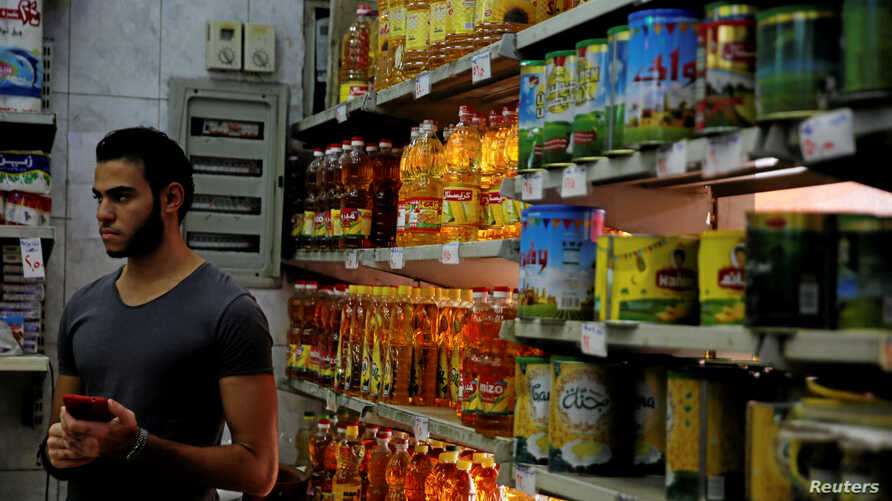 A worker goes about his day while waiting for customers at a supermarket in Cairo, Egypt, Oct. 26, 2016.