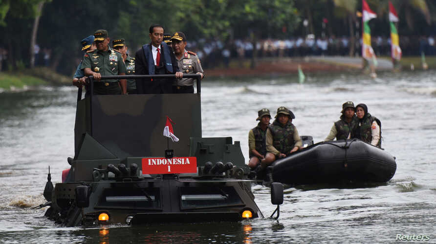 (L-R) Indonesia Military Chief Gatot Nurmantyo, Indonesia President Joko Widodo, and Indonesia Police Chief Tito Karnavian stand on a military amphibious vehicle Anoa 2 while crossing a lake at a military headquarters in Jakarta, Jan. 16, 2017,  in t
