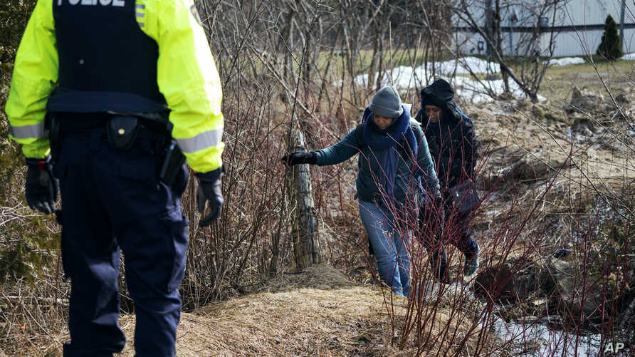 Two people who later indicated to officials they are from Sudan cross into Canada from Perry Mills, N.Y., near Hemmingford, Quebec, Feb. 26, 2017.