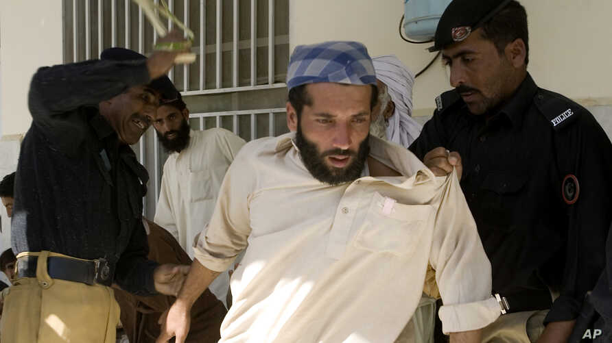 FILE - Pakistani police officers beat an internal displaced person who fled Pakistani tribal area of Waziristan due to fierce fight between security forces and militants, as they wait for food relief in Paharpur near Dera Ismail Khan, Pakistan, Oct.