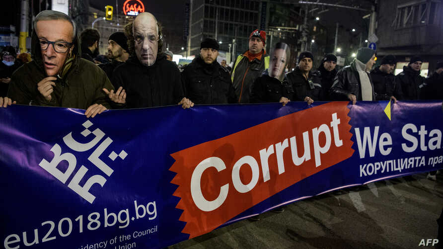 Bulgarian anti-corruption protesters wear masks during a demonstration in downtown Sofia, Jan. 11, 2018.