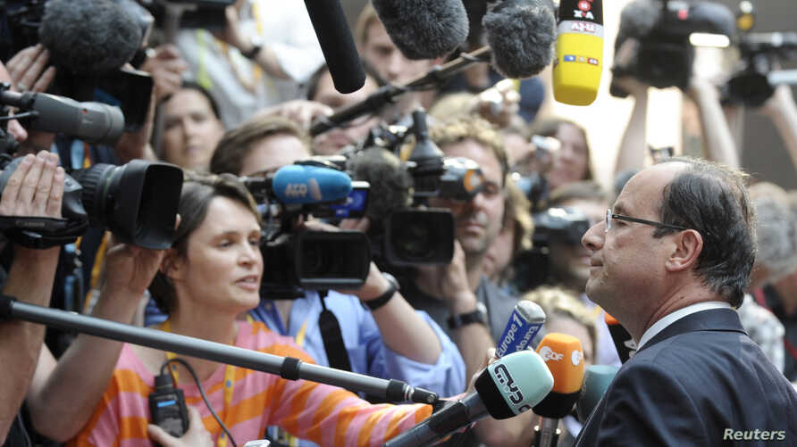 France's President Francois Hollande (R) talks to the media as he arrives at an informal EU leaders summit in Brussels, May 23, 2012.
