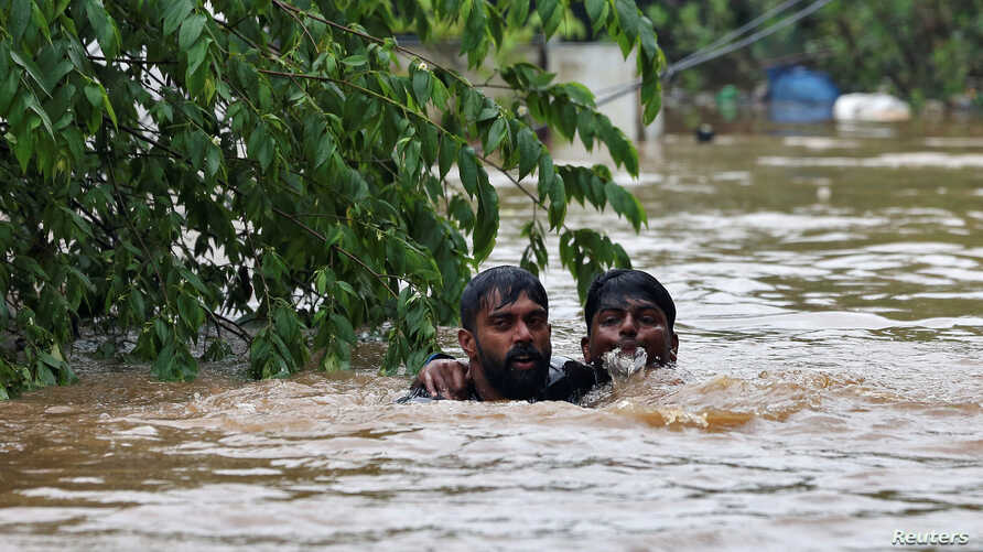 A man rescues a drowning man from a flooded area after the opening of Idamalayr, Cheruthoni and Mullaperiyar dam shutters following heavy rains, on the outskirts of Kochi, India, Aug. 16, 2018.