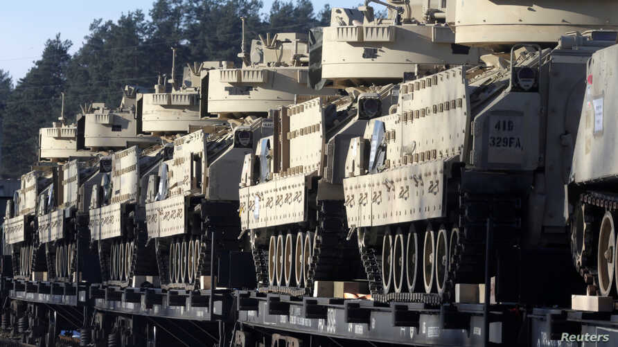 U.S. Bradley fighting vehicles that will be deployed in Latvia for NATO's Operation Atlantic Resolve wait to be unloaded in Garkalne, Latvia Feb. 8, 2017.