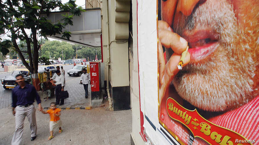 FILE - A man and child walk past advertisement showing Bollywood star Bachchan smoking in one of his films, in Bombay, India.