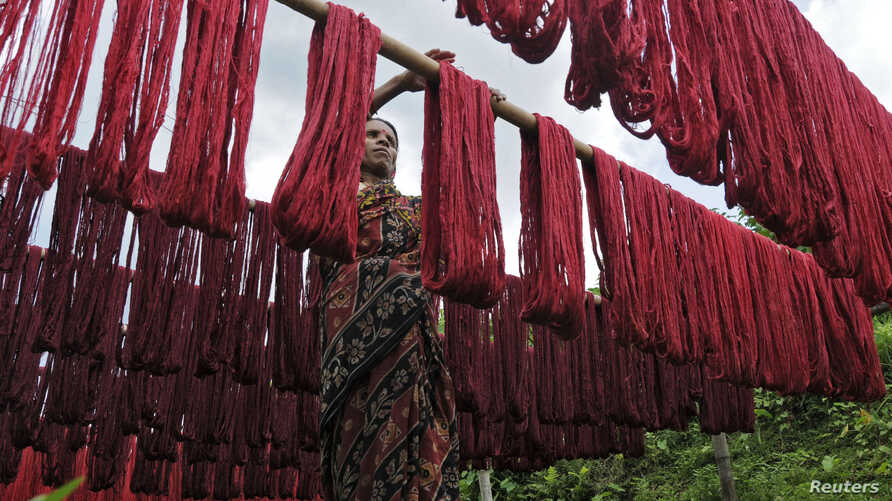 FILE - A woman hangs dyed yarn to dry at a textile mill in India, June 11, 2010.