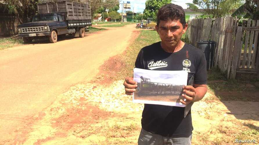 Displaced farmer Manuel Freitas Camurca poses for a photo holding a picture of his house that was destroyed during a land conflict with a powerful rancher in Boca do Acre, Amazonas State, Brazil, May 24, 2017.