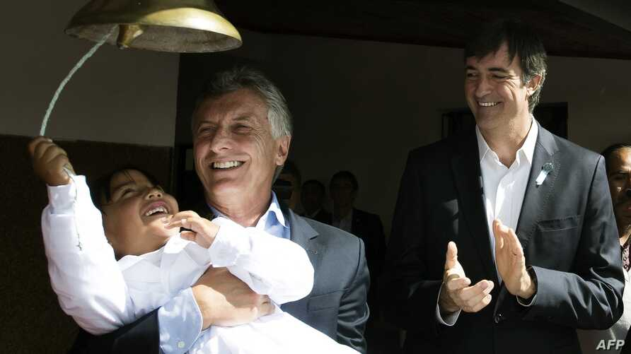 FILE - A handout picture released by Argentina's Presidency shows Argentine President Mauricio Macri holding a school girl while she rings a bell next to then Education Minister Esteban Bullrich during an official ceremony to launch the school year i