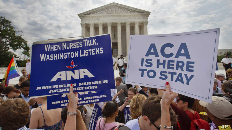 Supporters of the Affordable Care Act hold up signs as the opinion for health care is reported outside of the Supreme Court in Washington, June 25, 2015.