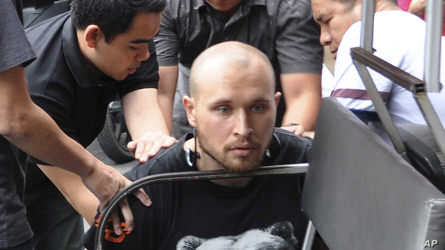 In this photo released by the Crime Suppression Division of the Thailand Police, Sergey Medvedev, 31 (C) is arrested outside an apartment for his role in an international identity theft ring that sold stolen credit card information on the dark web, l