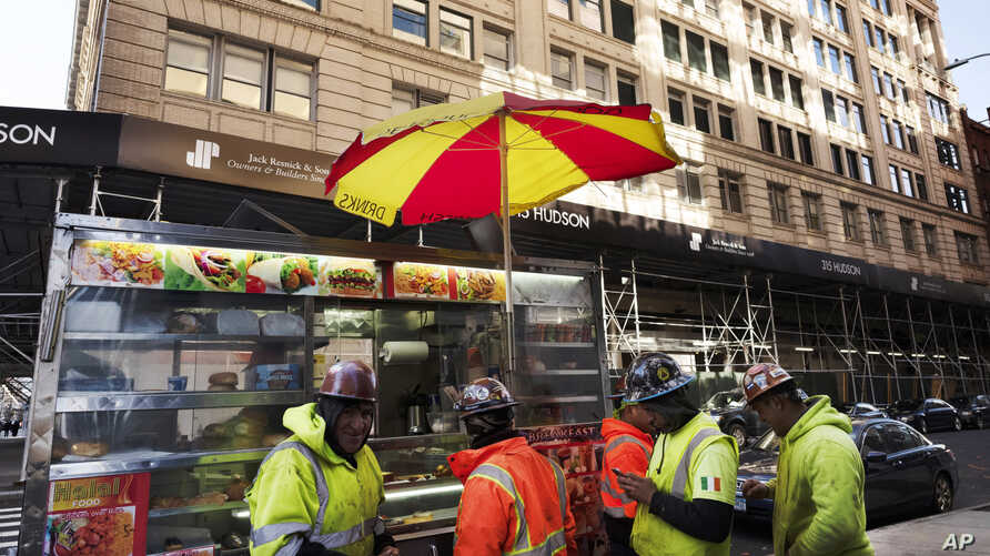 Construction workers buy food from a street cart in front of a building that has been chosen by Google as part of its expansion plans in New York, Dec. 17, 2018.