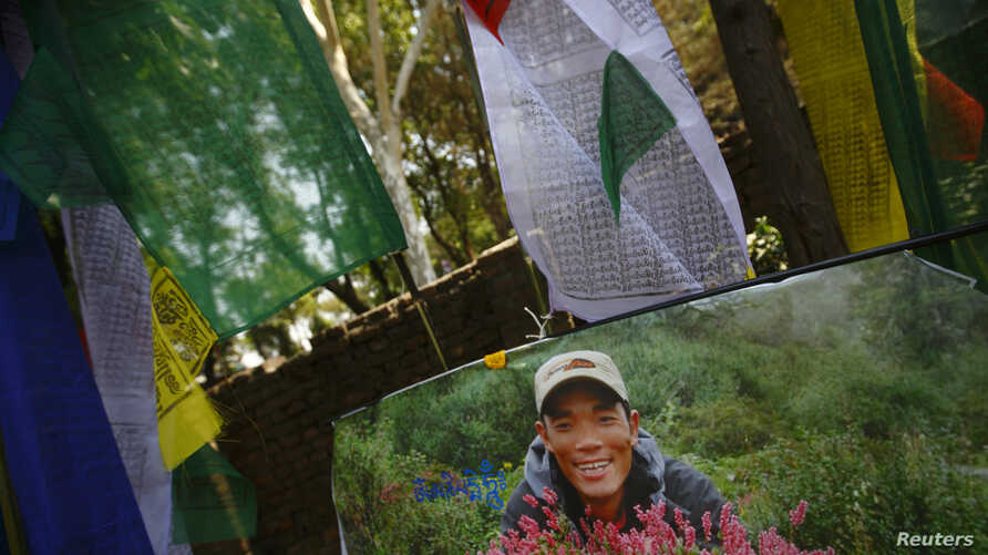 A portrait of Ankaji Sherpa, who lost his life in an avalanche at Mount Everest last Friday, is seen near a prayer flag during the cremation ceremony of Nepali Sherpa climbers in Kathmandu, April 21, 2014.